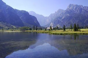 Fjellen lager et gjenskinn i en speilblank Almsee, Oberösterreich, Østerrike.